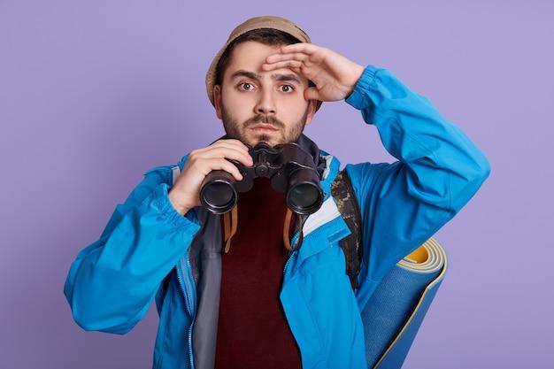 Jonge man die afstand met hand dichtbij voorhoofd onderzoekt