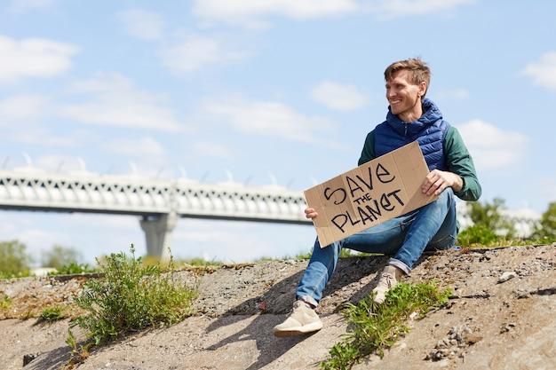 Jonge man die als vrijwilliger werkt, houdt plakkaat vast en kijkt weg terwijl hij buiten zit