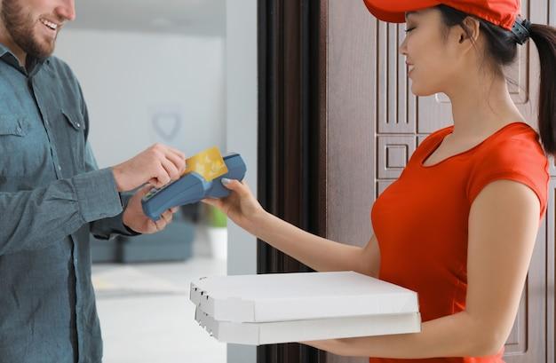 Jonge man die bankterminal gebruikt voor creditcardbetaling bij deuropening. maaltijden bezorgservice