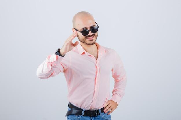 Jonge man die begroetingsgebaar in roze shirt, spijkerbroek, zonnebril toont en er vrolijk uitziet, vooraanzicht.
