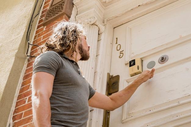 Jonge man die bij een vriendendeur belt