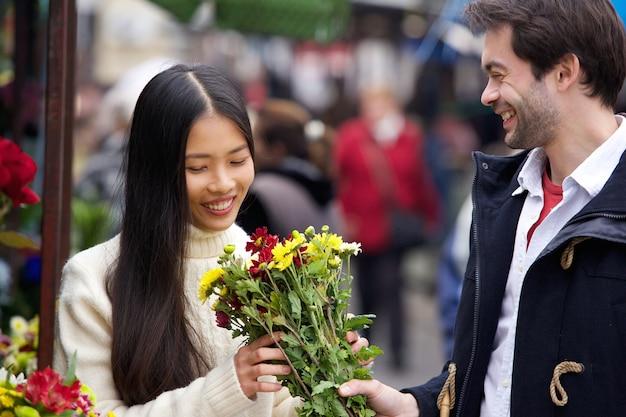 Jonge man die bloemen geeft aan mooie vrouw