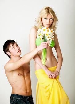 Jonge man die bloemen presenteert aan blonde mooie vrouw in groene bikini en geel