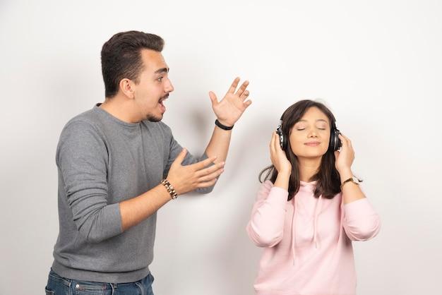 Jonge man die boos is over het constante geluid van de vrouw.