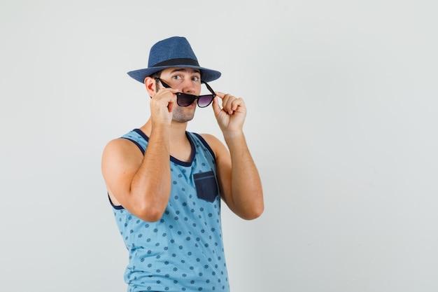 Jonge man die bril in blauw hemd, hoed opstijgt en gefocust kijkt. vooraanzicht.