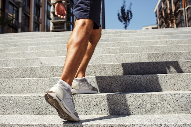 Jonge man die buiten traint. gesneden zicht op sterke krachtige benen en voeten in sneakers. gespierde kuit. man loopt op trappen bij stedelijk gebouw. nog een stap. Premium Foto
