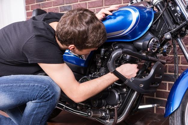 Jonge man die bukt om aan zijn motor te sleutelen om de prestaties te verbeteren, van achteren gezien in vrijetijdskleding