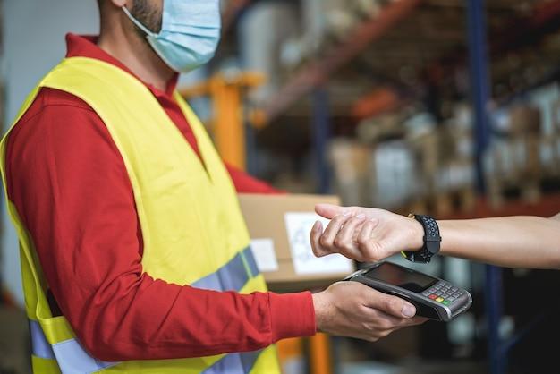 Jonge man die contactloos betalen in warenhuis tijdens uitbraak van coronavirus - focus op smartwatch