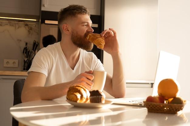Jonge man die croissant eet en thee of koffie drinkt bij het ontbijt. doordachte europese bebaarde man zit aan tafel met eten en laptop. interieur van keuken in modern appartement. zonnige ochtendtijd