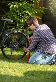 Jonge man die de achterband van een fiets oppompt in het park