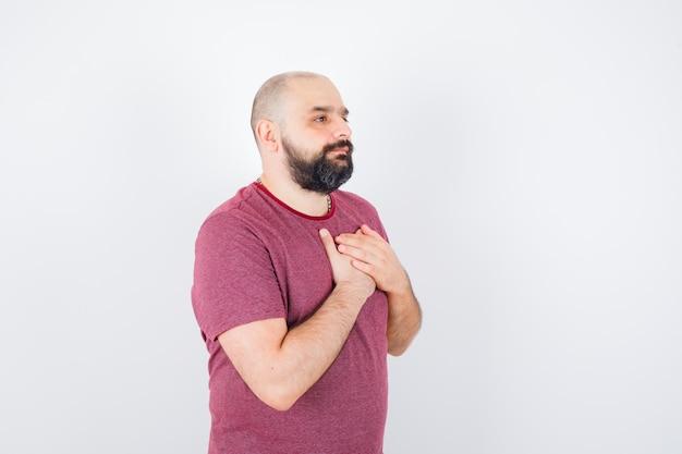 Jonge man die de hand op de borst houdt in een roze t-shirt en er hoopvol uitziet.