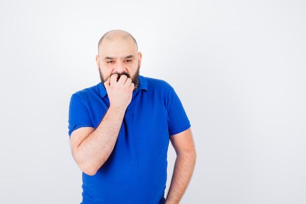 Jonge man die de hand op de mond houdt in een blauw shirt en er opgewonden uitziet. vooraanzicht.