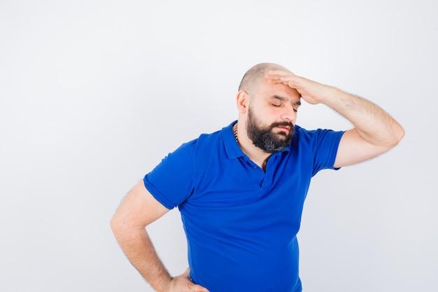 Jonge man die de hand op het hoofd houdt in een blauw shirt en er stressvol uitziet. vooraanzicht.