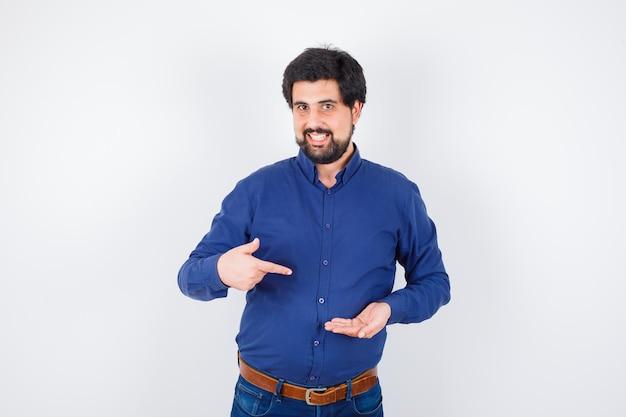 Jonge man die de hand uitstrekt en ernaar wijst in een blauw shirt en spijkerbroek en er optimistisch uitziet. vooraanzicht.