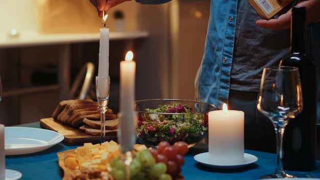 Jonge man die de kaars aansteekt en haar vrouw wacht op een romantisch diner. man bereidt feestelijke maaltijd met gezond voedsel voor jubileumviering, romantische date, zittend in de buurt van de tafel in de keuken.