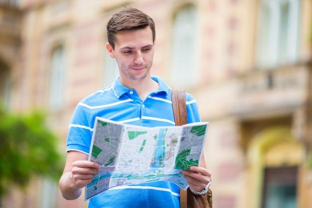 Jonge man die de straat zoekt met een plattegrond van de stad in europa. kaukasische toerist die de kaart van europese stad bekijkt op zoek naar aantrekkelijkheden.