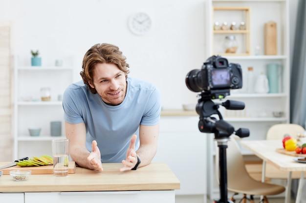 Jonge man die de video maakt die hij vertelt over het gezonde eten aan zijn volgers terwijl hij in de keuken staat