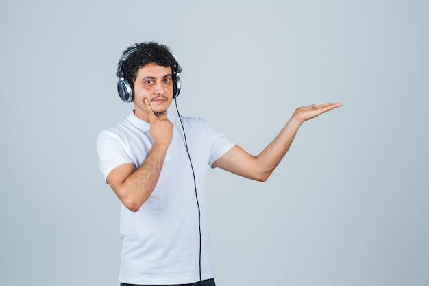 Jonge man die de vinger op de wang houdt, de palm opzij spreidt in een wit t-shirt en er attent uitziet, vooraanzicht.