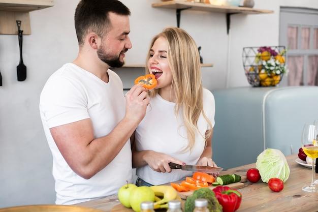 Jonge man die de vrouw met groene paprika voedt