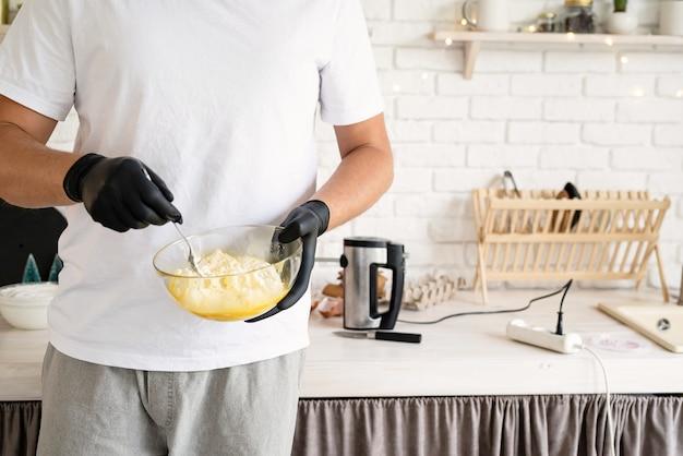 Jonge man die deeg in de keuken maakt