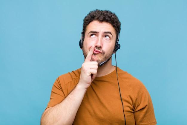 Jonge man die denkt, twijfelachtig en verward voelt, met verschillende opties, zich afvraagt welke beslissing hij moet nemen
