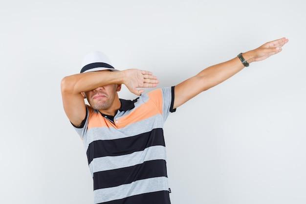 Jonge man die deppen beweging in t-shirt en hoed maakt en vrolijk kijkt