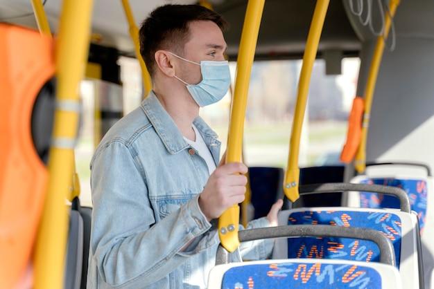 Jonge man die door stadsbus reist die chirurgisch masker draagt