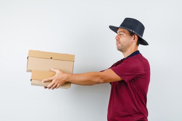 Jonge man die dozen in rood overhemd, zwarte hoed overhandigt en kalm kijkt. .