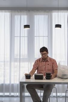Jonge man die dozen voor voedselbezorging sorteert in de moderne keuken