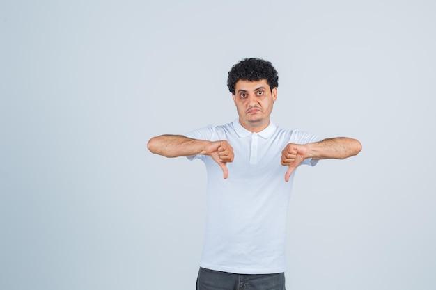 Jonge man die duimen naar beneden toont met beide handen in een wit t-shirt en spijkerbroek en er serieus uitziet. vooraanzicht.