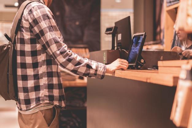 Jonge man die een aankoop doet en betaalt bij de kassa in de winkel