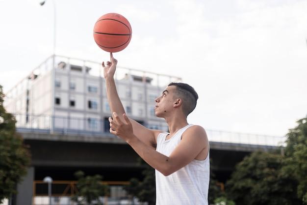 Jonge man die een basketbal op zijn wijsvinger spint