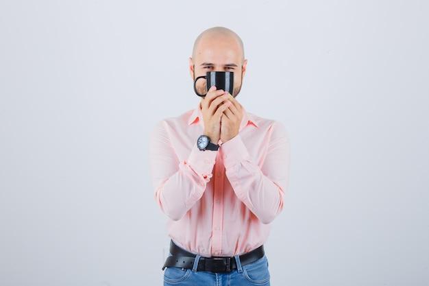 Jonge man die een beker vasthoudt terwijl hij eroverheen kijkt in een roze shirt, jeans vooraanzicht.