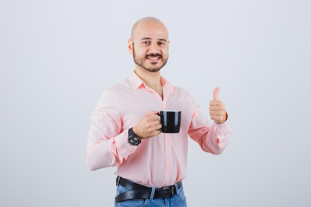 Jonge man die een beker vasthoudt terwijl hij zijn duim in een roze shirt laat zien, jeans vooraanzicht.
