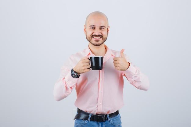 Jonge man die een beker vasthoudt terwijl hij zijn duim in een roze shirt, spijkerbroek laat zien en er vrolijk uitziet, vooraanzicht.