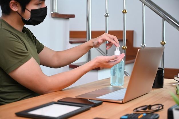 Jonge man die een beschermend masker draagt en alcoholgel uit een pompfles gebruikt.
