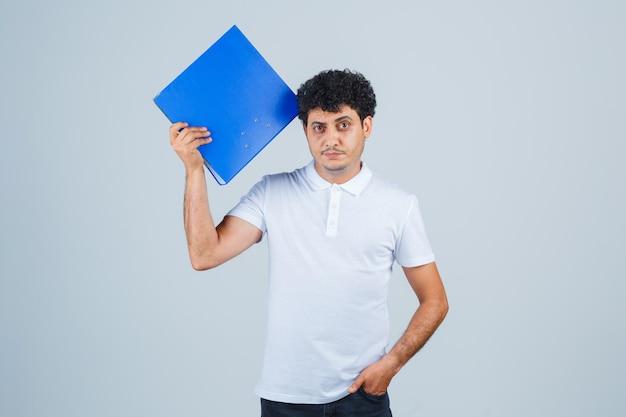 Jonge man die een bestandsmap vasthoudt en een hand in de zak houdt in een wit t-shirt en een spijkerbroek en er serieus uitziet. vooraanzicht.