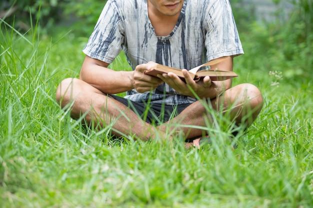 Jonge man die een boek in het park leest