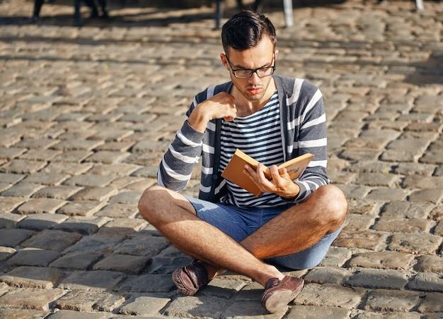 Jonge man die een boek leest. hij zit op de stoep