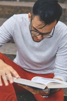 Jonge man die een boek leest op de campus