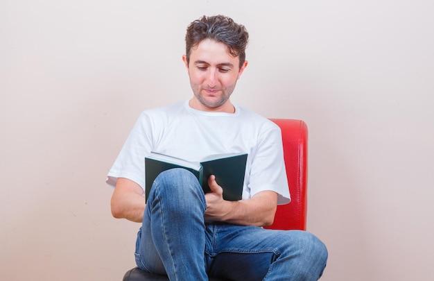 Jonge man die een boek leest terwijl hij op een stoel zit in een t-shirt, spijkerbroek en er vrolijk uitziet