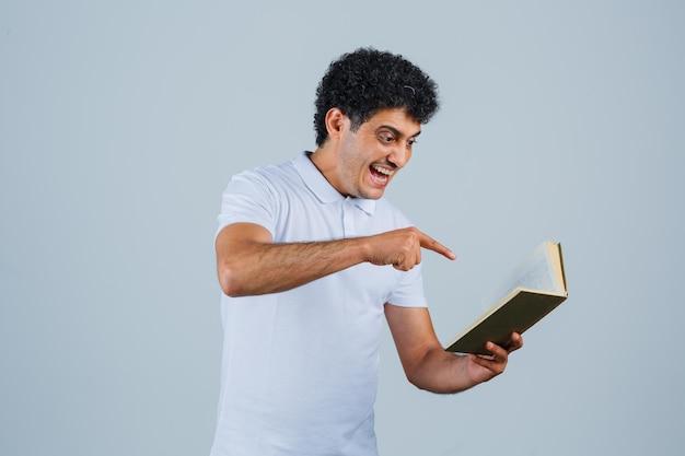 Jonge man die een boek vasthoudt en ernaar wijst in een wit t-shirt en spijkerbroek en er gelukkig uitziet, vooraanzicht.