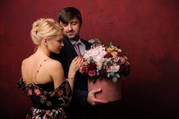 Jonge man die een boeket bloemen houdt in de buurt van zijn vrouw
