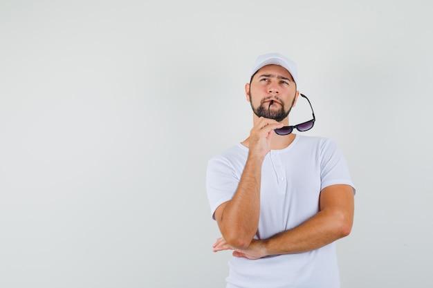 Jonge man die een bril bijt terwijl hij opkijkt in een wit t-shirt en peinzend kijkt. vooraanzicht. ruimte voor tekst Gratis Foto