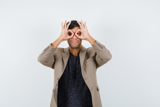 Jonge man die een brilgebaar toont met zijn vingers in een grijsachtig bruin jasje, een zwart shirt en er grappig uitziet. vooraanzicht.