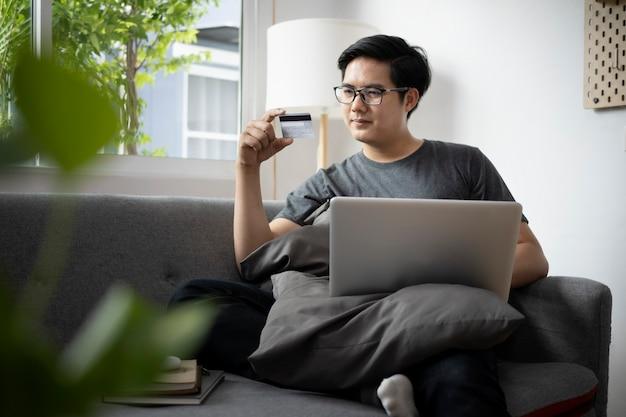 Jonge man die een creditcard vasthoudt en een laptop gebruikt om thuis online te winkelen of online te bankieren.