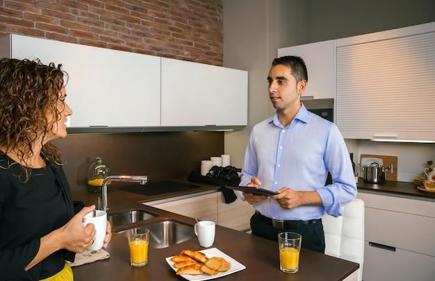 Jonge man die een elektronische tablet vasthoudt terwijl hij praat met een gekrulde vrouw bij het ontbijt voordat hij naar zijn werk gaat