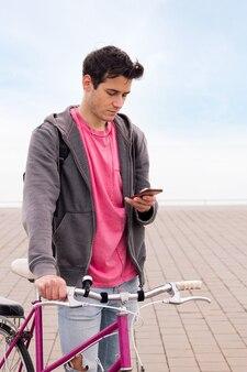 Jonge man die een fiets vasthoudt en op zijn smartphone kijkt