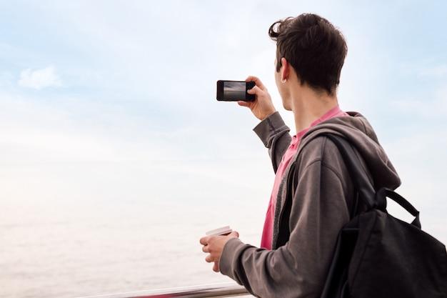 Jonge man die een foto maakt met een mobiele telefoon