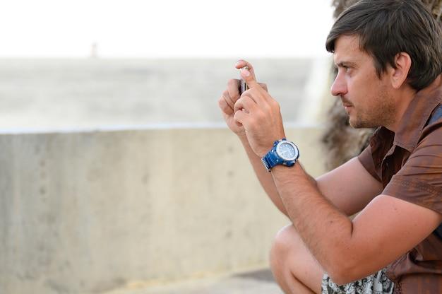 Jonge man die een foto-opname of videolandschap neemt met behulp van een mobiele telefoon